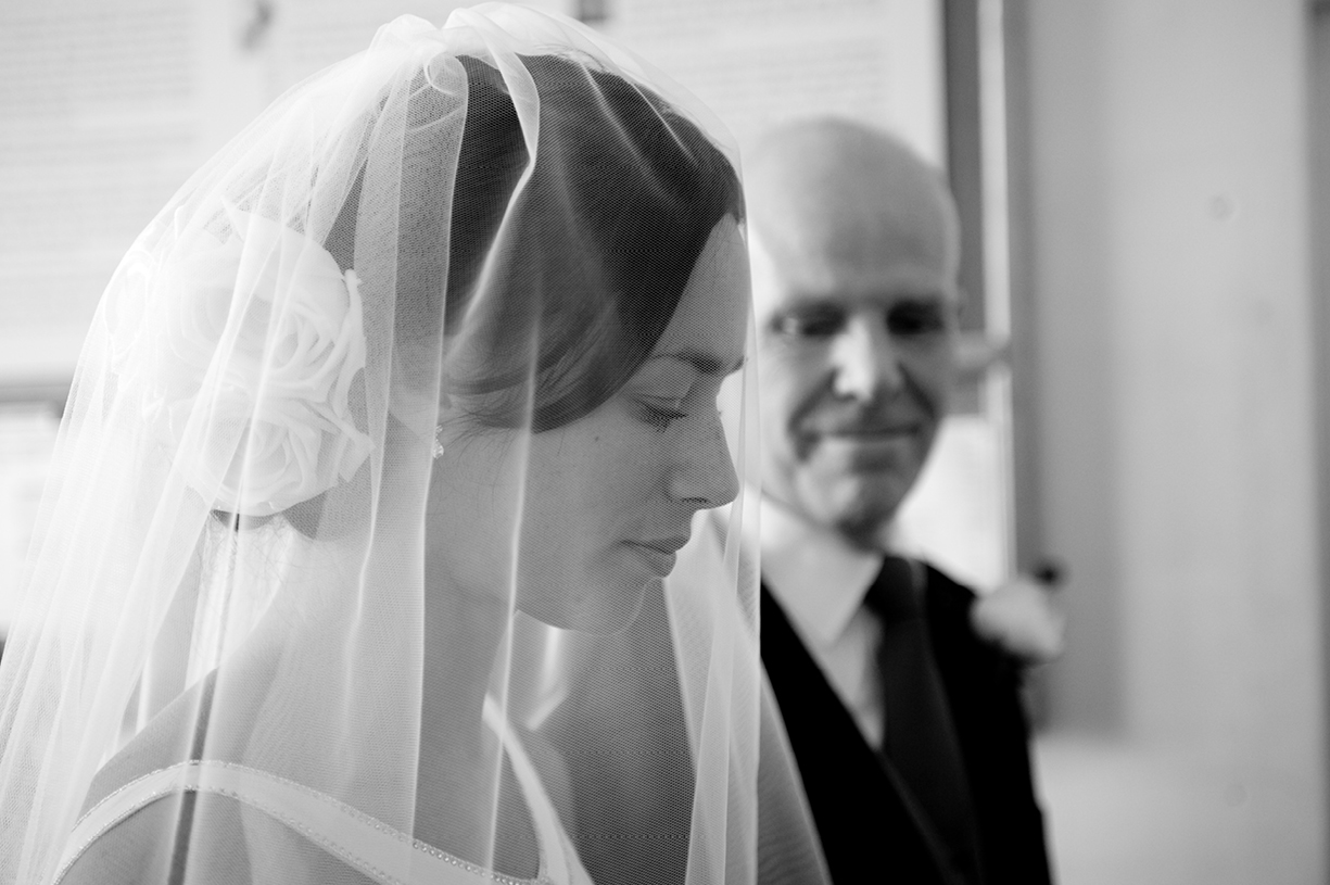 bride in veil at vestry waiting to go in black & white wedding photography Hampshire