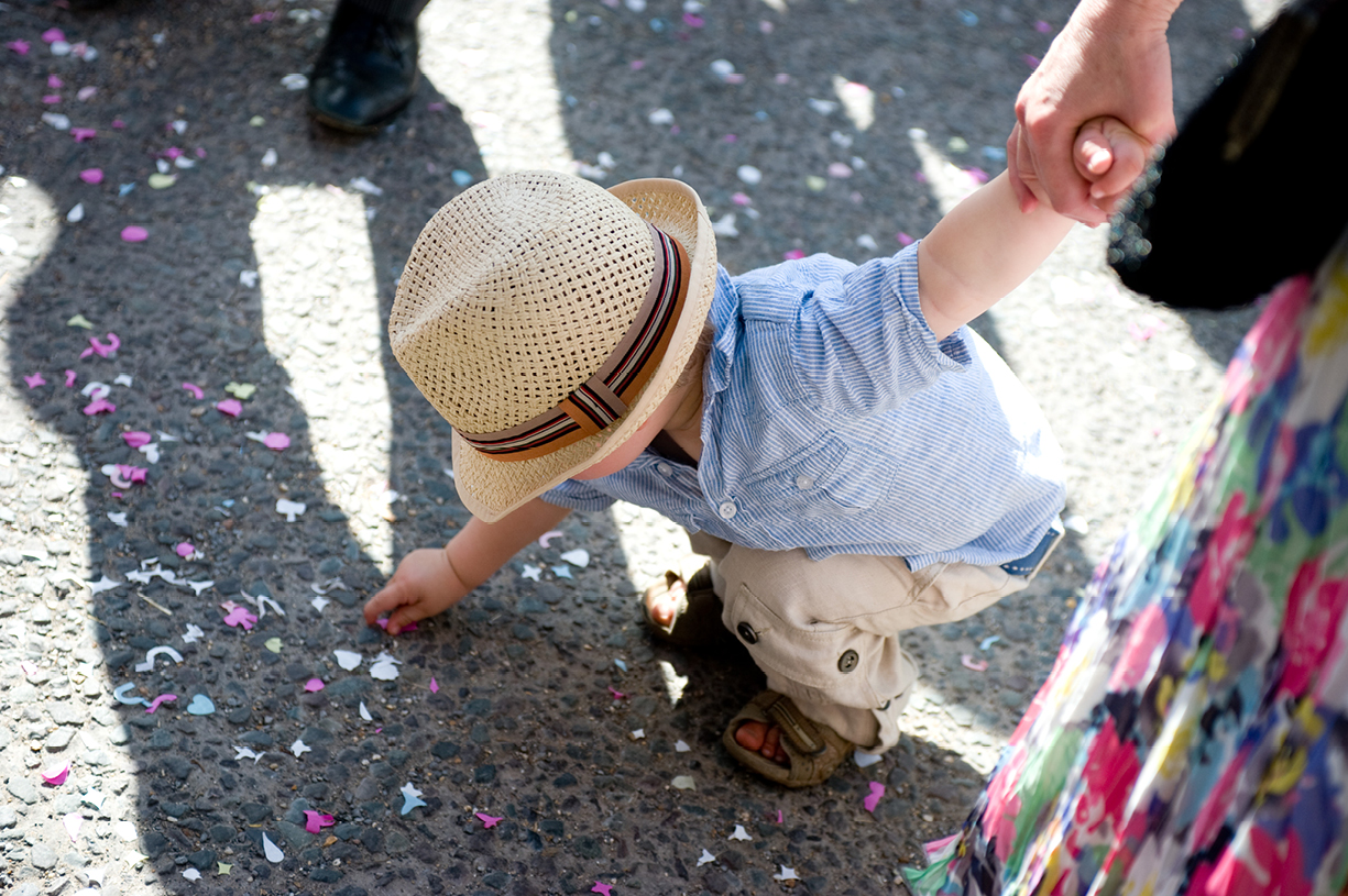 small boy collecting confetti summer wedding photography Alresford Hampshire