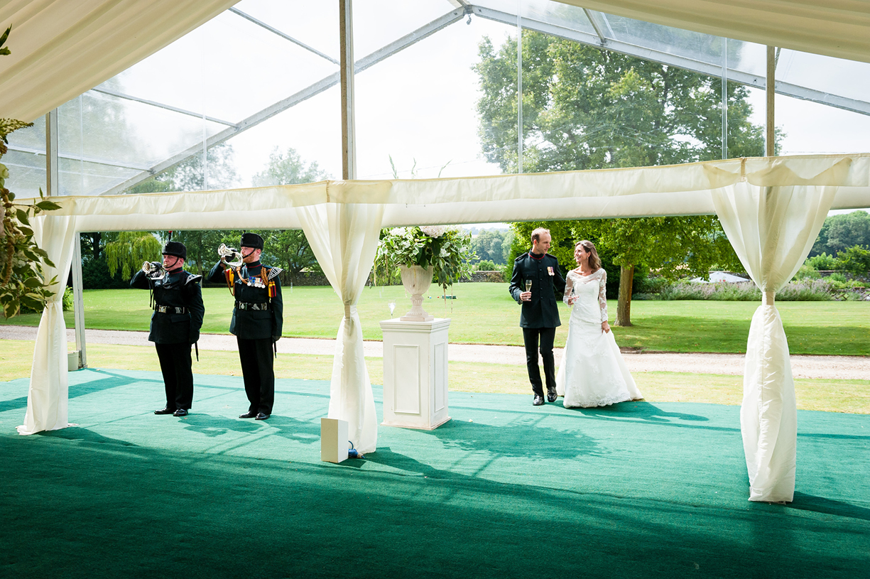 bride & groom enter marquee for wedding breakfast announced by Green Jackets buglers summer Ovington Hampshire