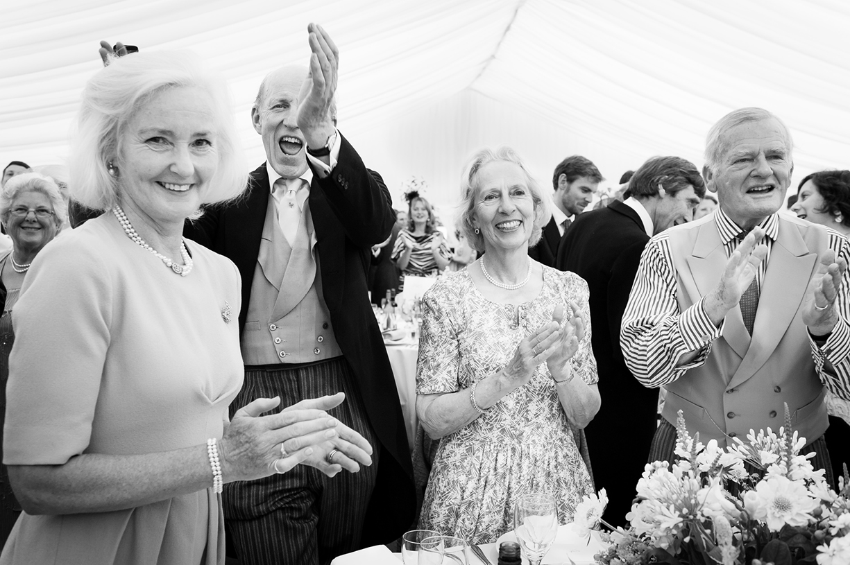 guests applaud arrival of bride & groom black & white summer wedding photography Ovington Hampshire