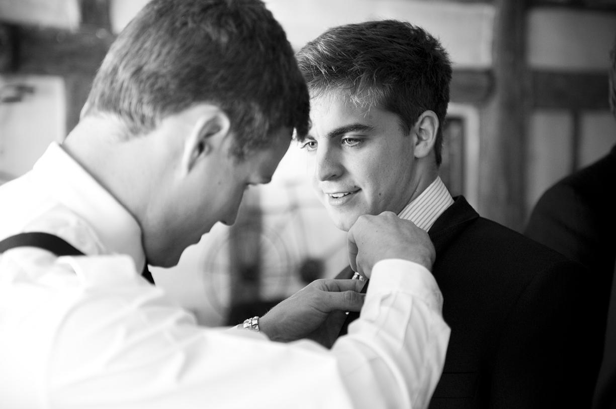 groom attaches buttonholes summer wedding Braintree Essex