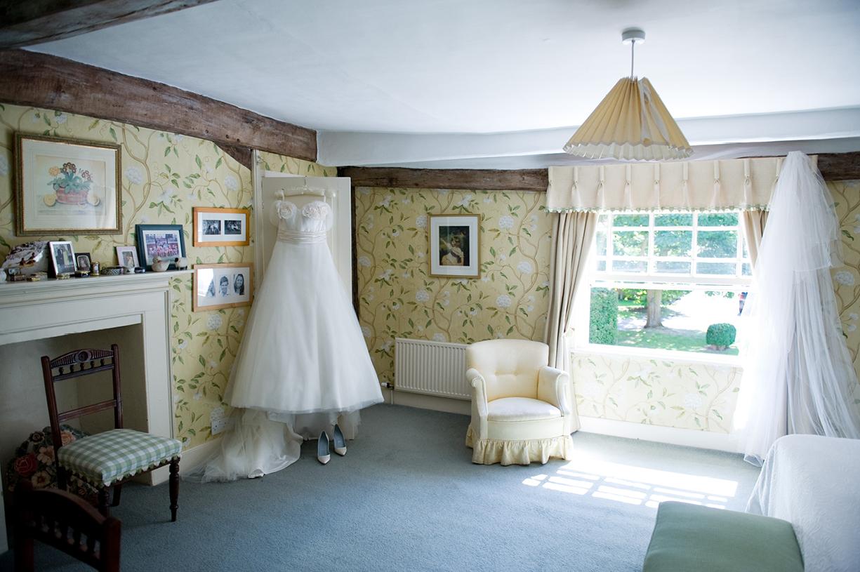 Philippa Lepley wedding dress hangs in bedroom hot sunny wedding Braintree Essex