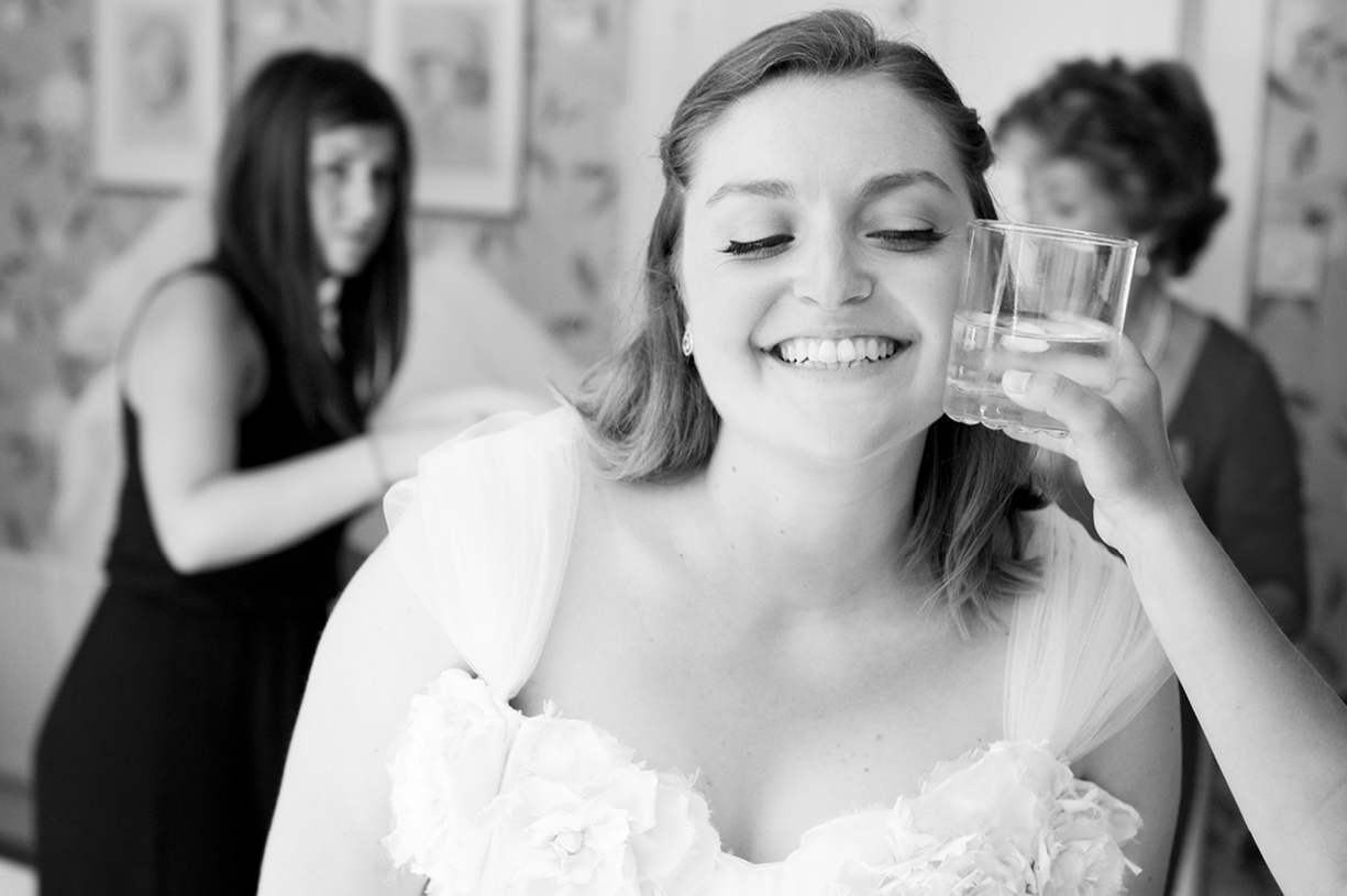 Philippa Lepley wedding dress bride cooled by iced water glass sunny wedding Braintree Essex black & white wedding photography