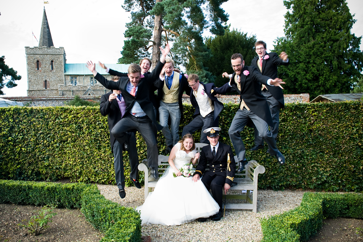 Philippa Lepley wedding dress ushers leaping in formal photograph wedding portraits sunny summer wedding Braintree Essex