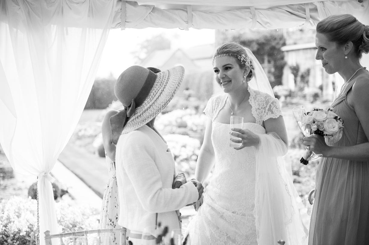 bride with guests black & white rainy wedding Buckhurst Park East Sussex wedding photography English & Greek