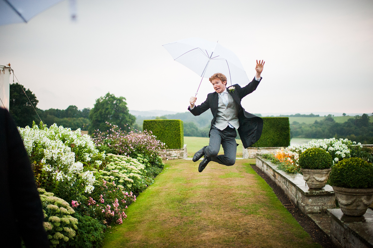guest leaps high with umbrella rainy wedding Buckhurst Park East Sussex wedding photography English & Greek