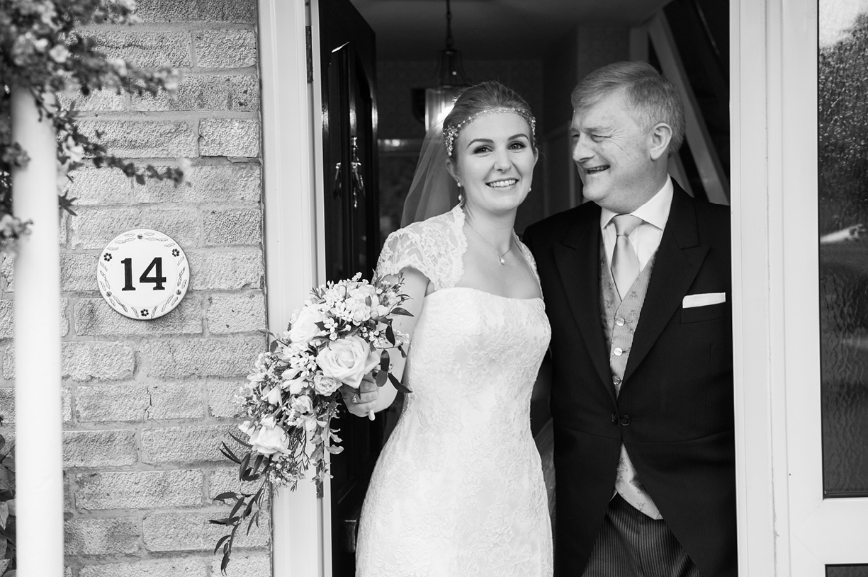 bride & father on doorstep black & white rainy wedding Buckhurst Park East Sussex wedding photography English & Greek