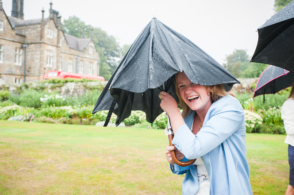 guest with umbrella rainy wedding Buckhurst Park East Sussex wedding photography English & Greek