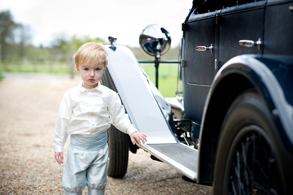 portrait photo of young pageboy admiring Rolls Royce while waiting for bride at summer wedding