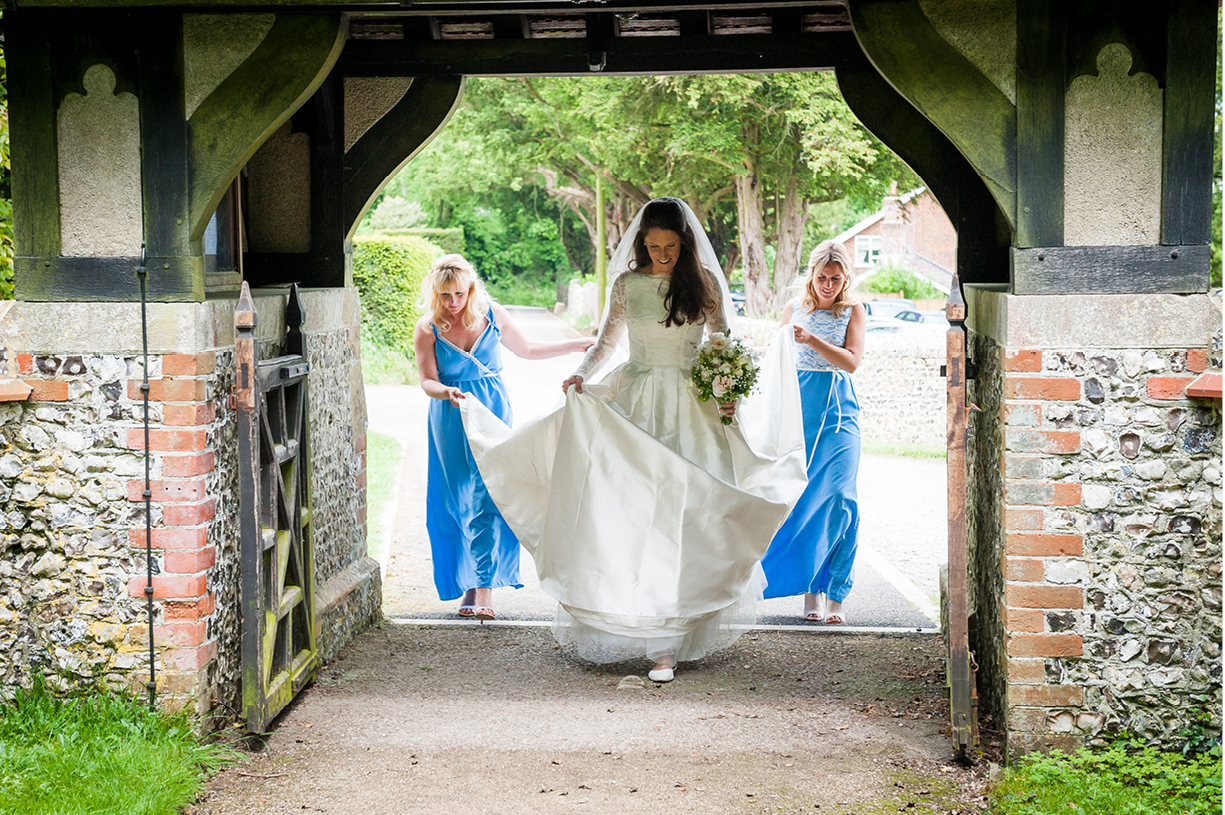 bride and maids of honour enter church gate at a Northington, Hampshire spring wedding