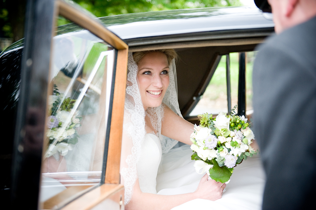 smiling bride arriving at church in Hertfordshire before reception at Munden Estates