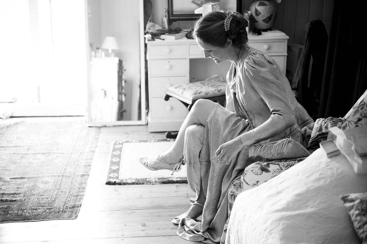 Dorset summer bride black & white wedding portrait putting on shoes backlit