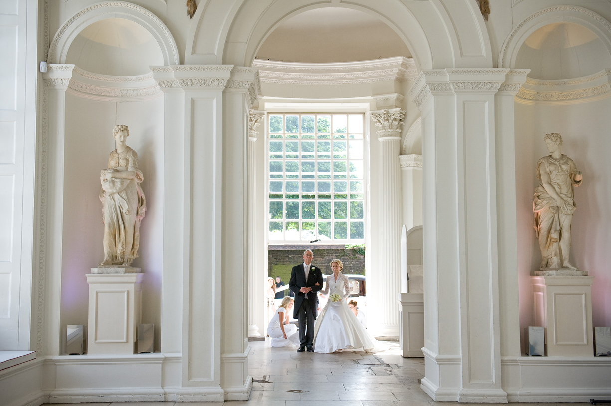 bride and father enter the Orangery at Kensington Palace, London, in Sassi Holford dress