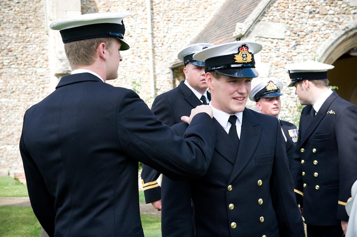 groom in naval uniform reassured by ushers before ceremony hot summer wedding Braintree Essex