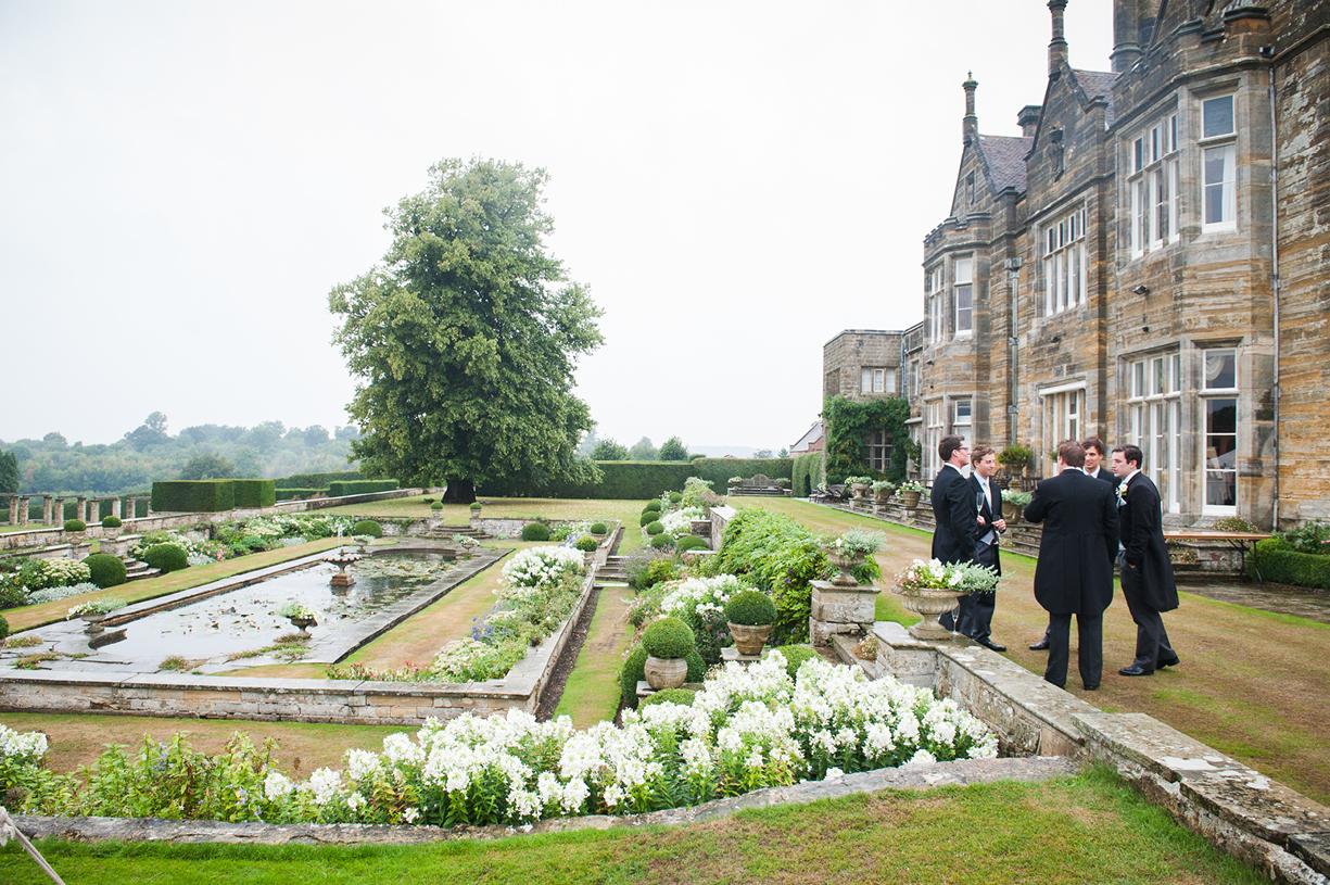 garden with guests rainy wedding Buckhurst Park East Sussex wedding photography English & Greek