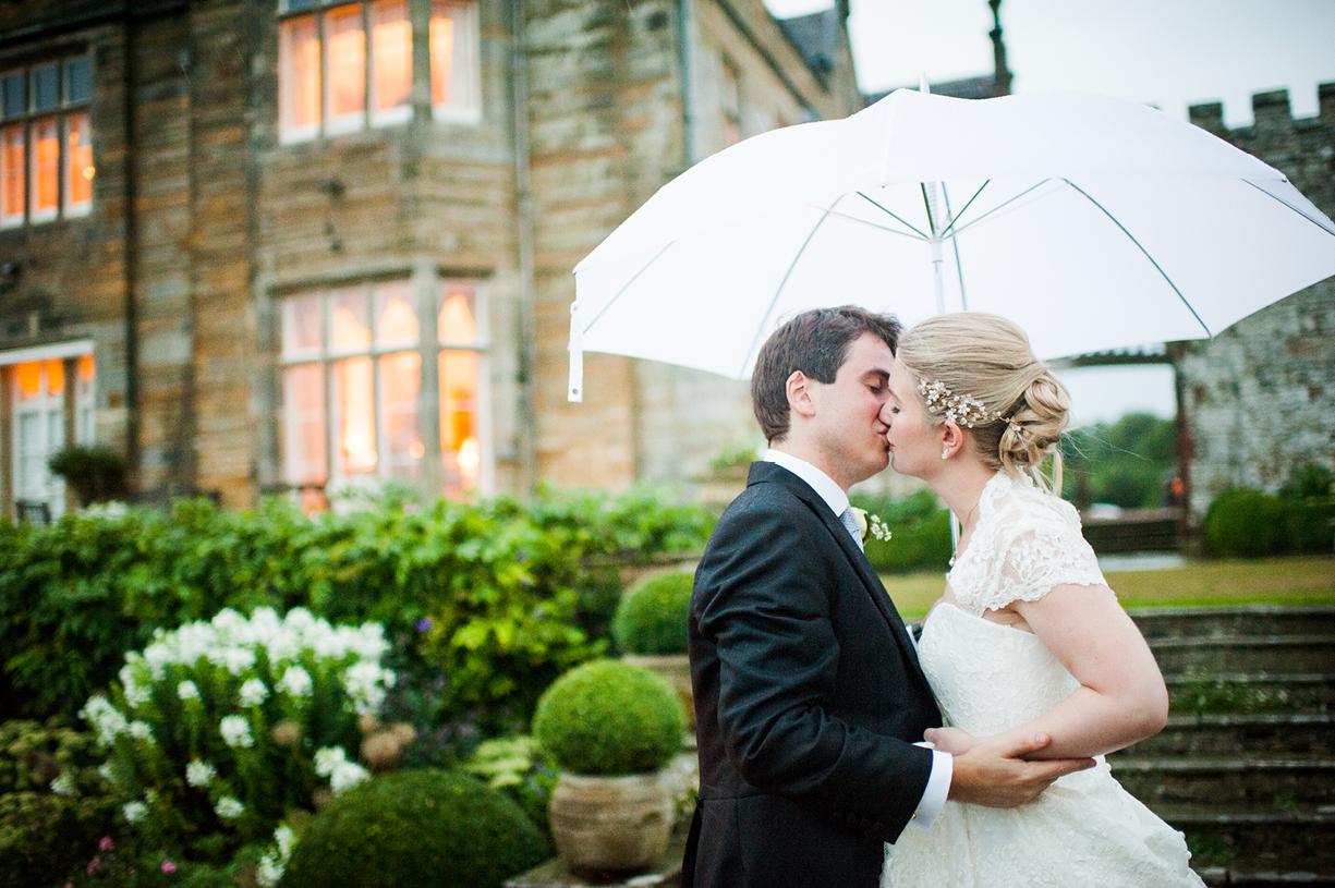 couple kissing with umbrella rainy wedding Buckhurst Park East Sussex wedding photography English & Greek