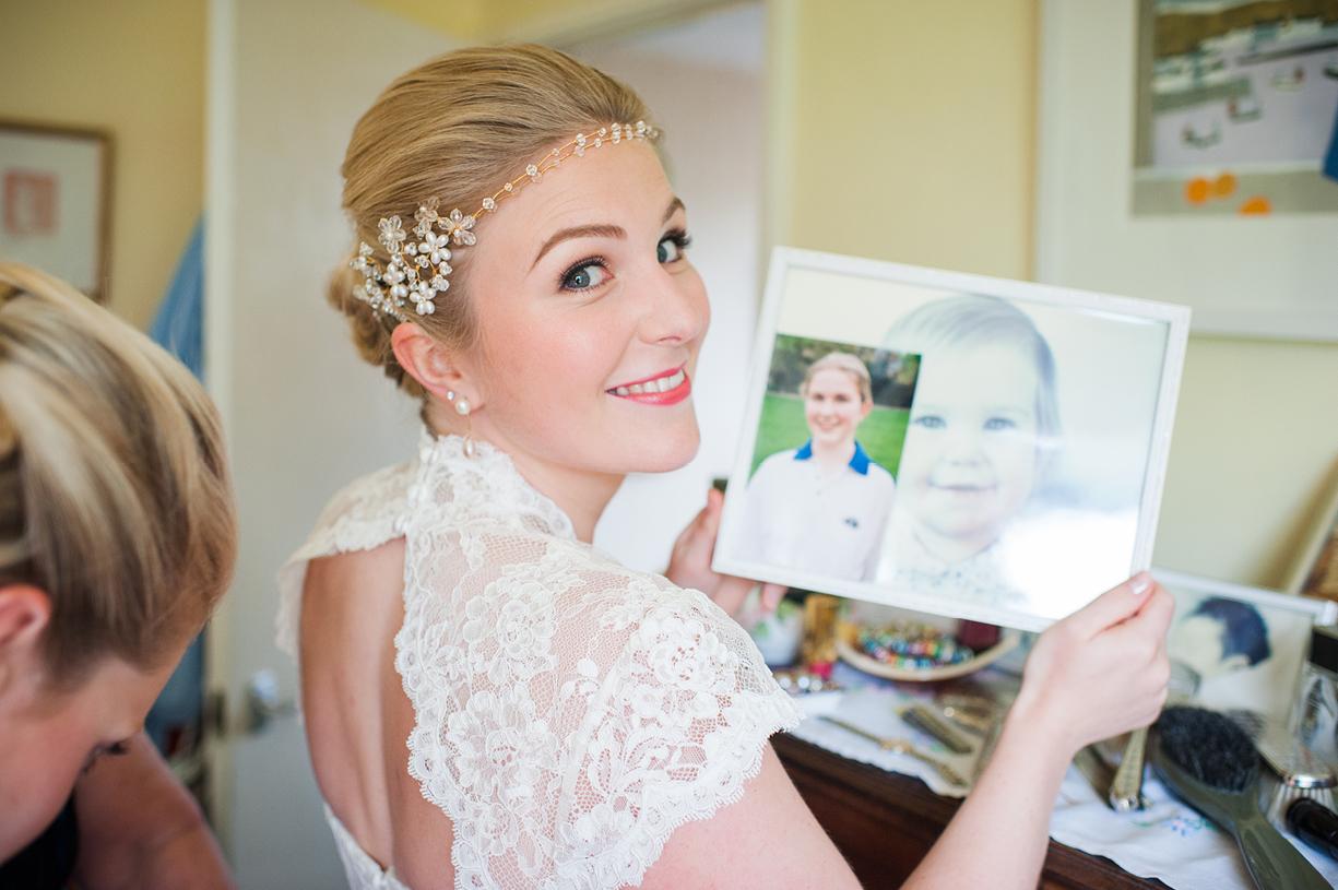 bride looks at childhood photos rainy wedding Buckhurst Park East Sussex wedding photography English & Greek