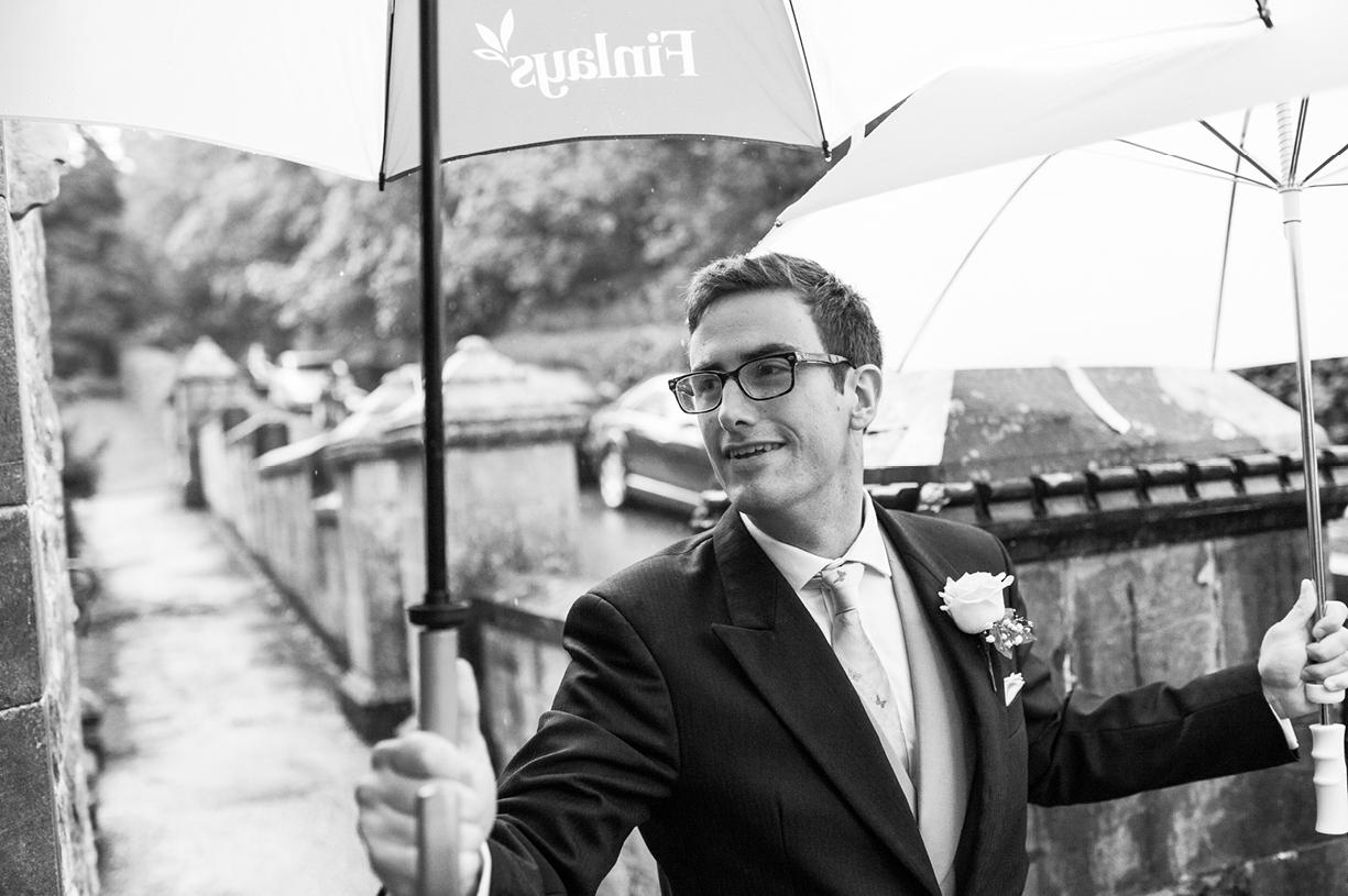 brother of the bride with umbrella rainy wedding Buckhurst Park East Sussex wedding photography English & Greek