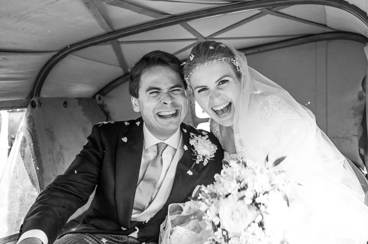 bride & groom laugh black & white rainy wedding Buckhurst Park East Sussex wedding photography English & Greek