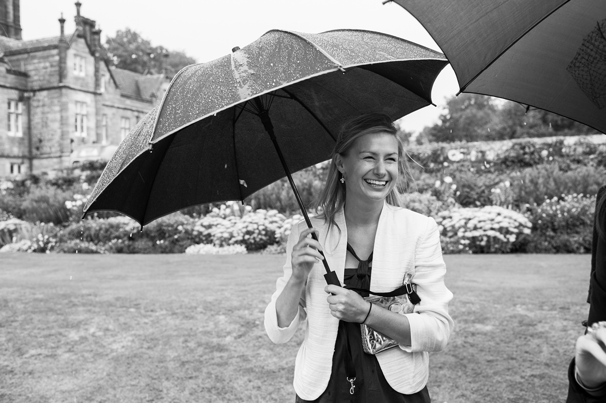 guest with umbrella rainy wedding Buckhurst Park East Sussex wedding photography English & Greek