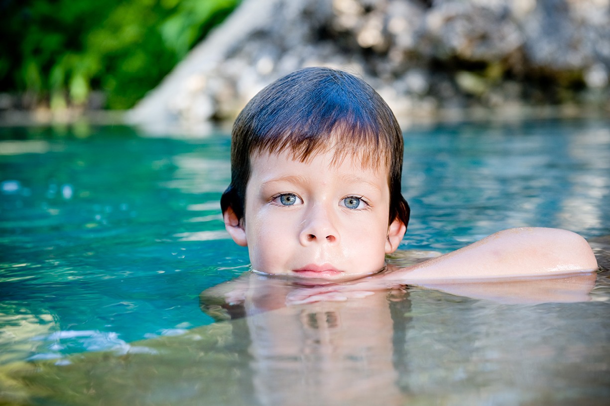 young boy colour portrait in swimming pool Kenya