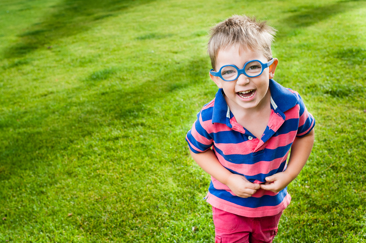 laughing colour portrait young boy with glasses in Hampshire