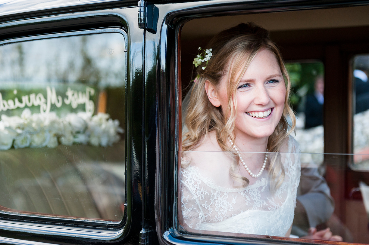 smiling bride in car 'just married' at Northington Church, Hampshire