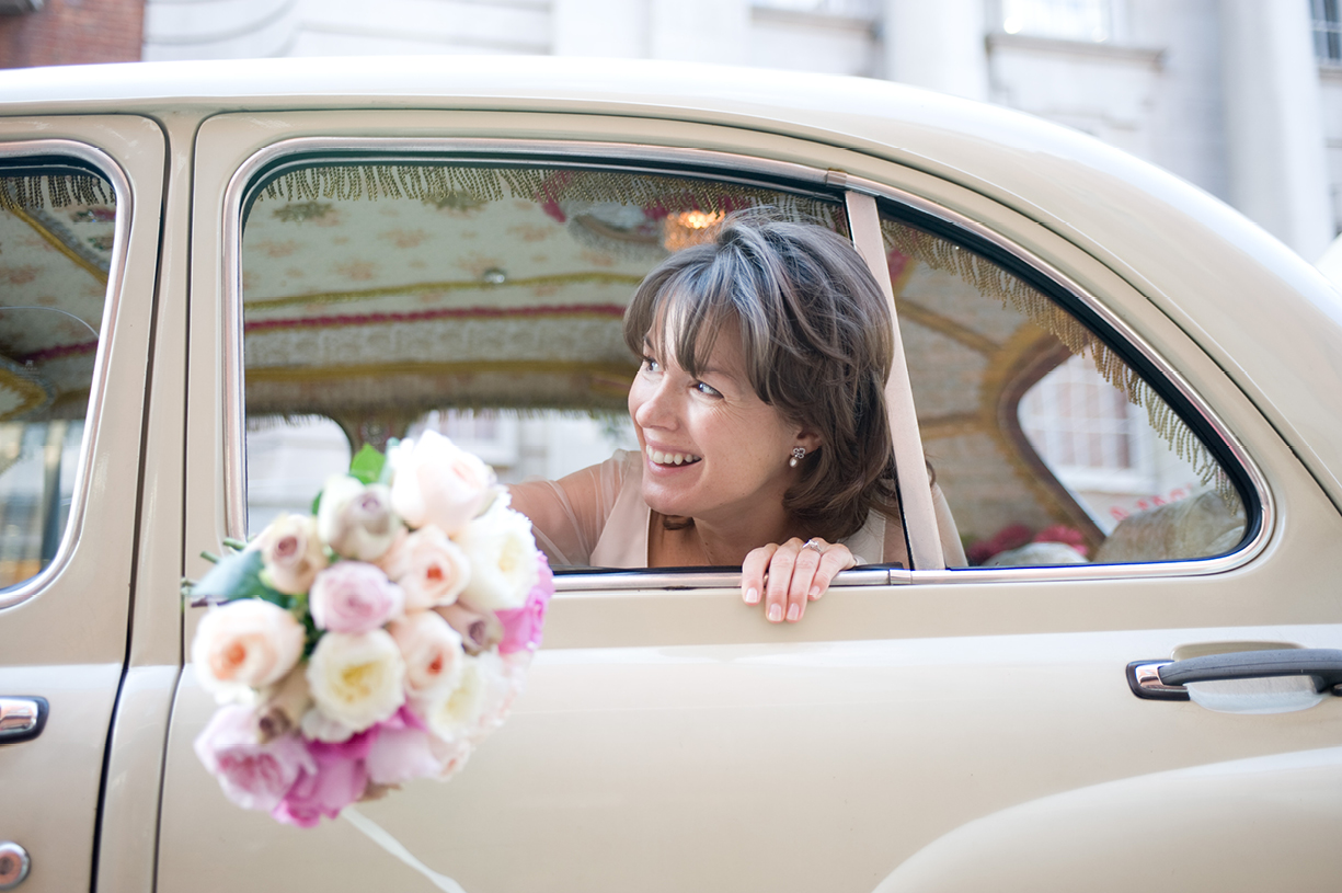 smiling bride arrives in Karma Kab at Chelsea Registry Office with roses