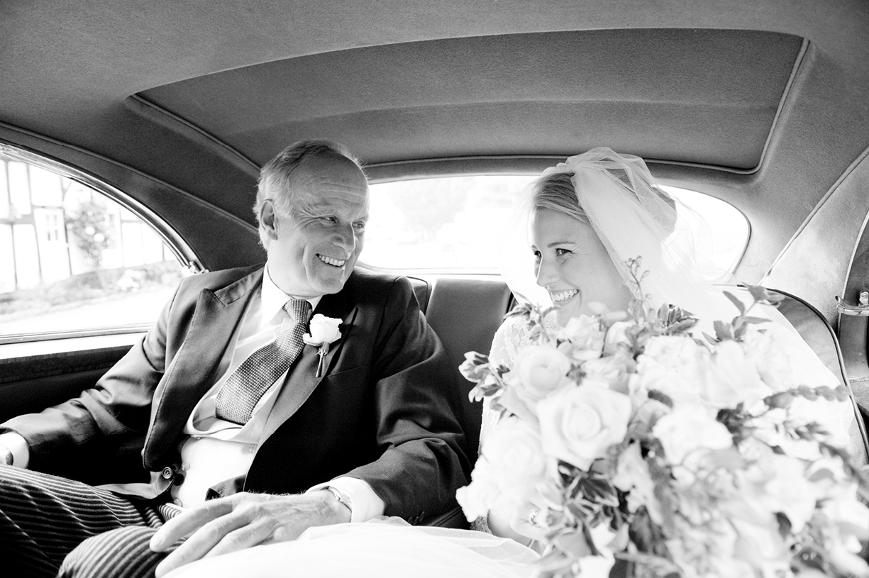 bride and father laughing Rolls Royce summer wedding black & white portrait