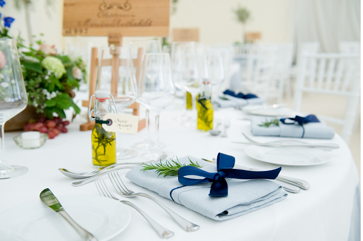 table setting with olive oil, ribbon, napkins, wineboxes, summer wedding at Munden Estates, Hertfordshire